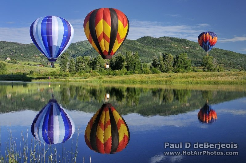 Three Hot Air Balloons and their reflections on the lake