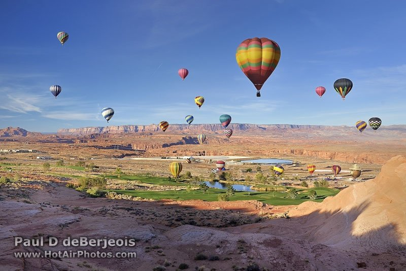 Many hot air balloons rising above the canyon