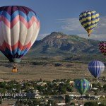Five Balloons Rising with Mountains Behind
