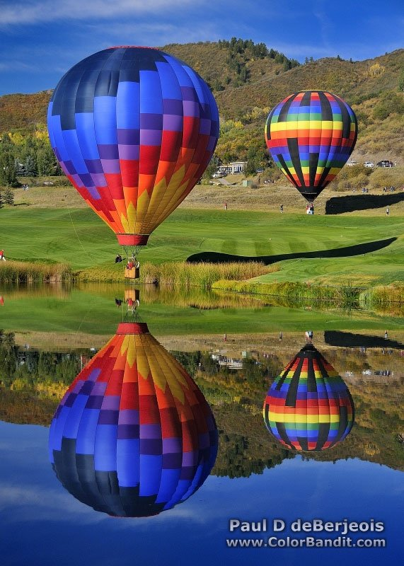 Two balloons shadows and reflections over golf course