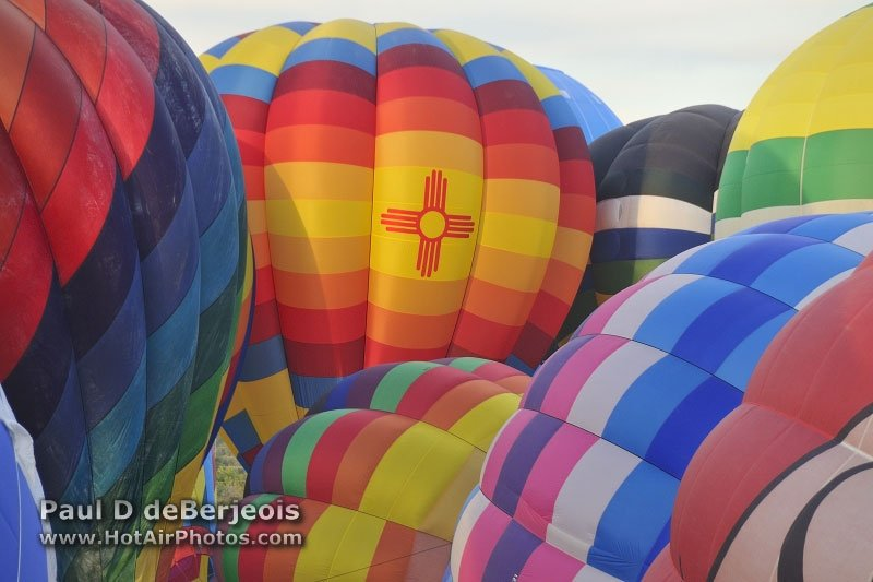 Sever hot air balloons inflating in close proximity