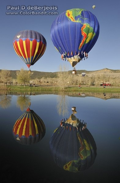 Two balloons and their reflection on the water